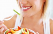 Cropped image of beautiful woman eating fresh vegetable salad